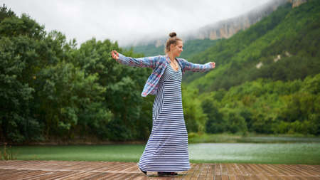Casual dressed hiking woman under the rain dancing near the lake in mountains. Candid and authentic expression. 版權商用圖片