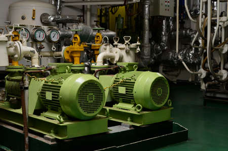 Engine room interior of a big ocean going ship with electrical motors, piping, gauges, valves etc.