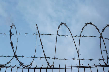 Barbed wire silhouette on a blue cloudy background as a border, privacy, quarantine or security concept. Zdjęcie Seryjne