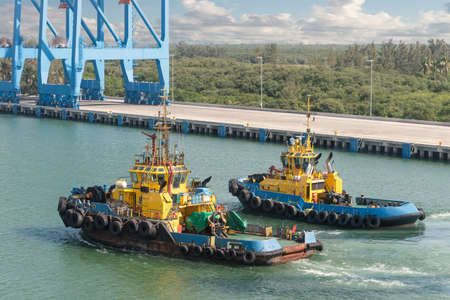 Tug boats awaiting big cargo ship in harbour for tug assistance, maneuvering, mooring operations. Tugboat and tow service concepts.