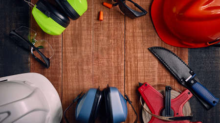 Construction site safety. Protective hard hat, headphones, gloves, glasses and masks on wooden background, copy space, top view Zdjęcie Seryjne