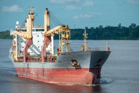 Multipurpose cargo ship underway in river delivering bulk cargo for international transshipment.