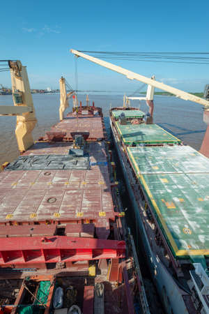 Two ships moored to each other at roads for performing double-banking operation for transportation reloading of bulk cargo.
