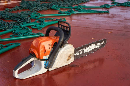 Chain saw laying on deck of ship and used for lashing of cargo. Cargo lashing and securing concept.