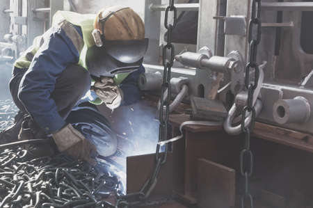 Welder doing welding on deck of ship lashing cargo for sea shipping on background of lenty lashing chains. Cargo securing concept. 版權商用圖片