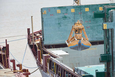 Loading and dischargind operation of bulk cargo bauxite on bulk carrier ship using grab bucket or clamshell.