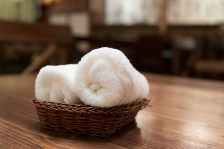 house ware: Basket of pure white towels on wooden table in japanese restaurant