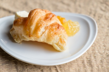Breakfast Croissant with pineapple jam and butter photo
