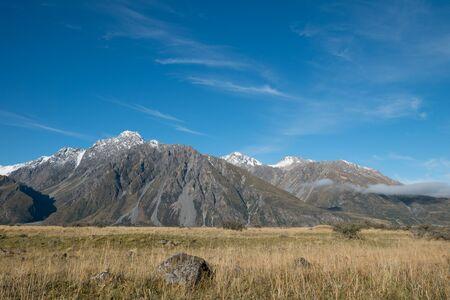 Meadow and Mountain Range with Blue Sky in Aoraki Mount Cook, South Island, New Zealand Standard-Bild