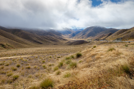 Lindis Pass Field and Mountain Range on Cloudy day, South Island, New Zealand