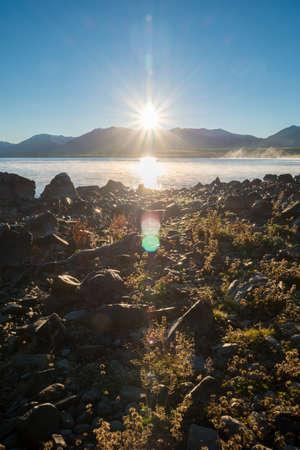 Lake Tekapo Sunrise with flare over mountain range, South Island, New Zealand