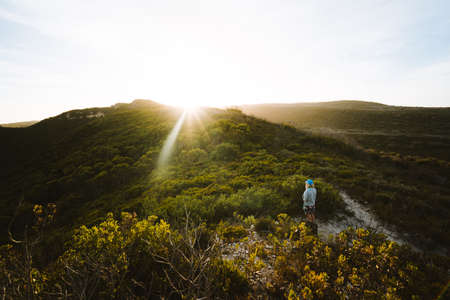 Girl standing alone in the middle of the South Australian bush, watching the golden sun set over the mountains in the background.