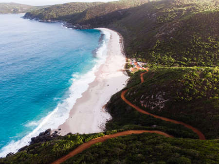 Aerial drone view of the coastal road that winds down to a quiet and remote bay in Albany, Australia.