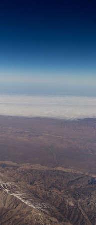 Clouds mountains and sky as seen through window of an aircraft of uzbekistan Stock Photo
