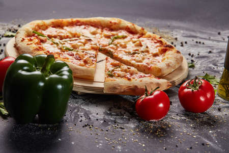 whole italian pizza on wood table with ingredients in black table