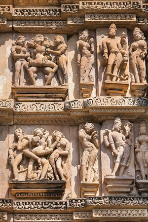 kamasutra: Cultural heritage of India - the sculptures made of sandstone, being couple in one of Kama-Sutra poses, on a wall of the temple of Kandariya-Mahadeva, Khajuraho, the Province of Madhya Pradesh.