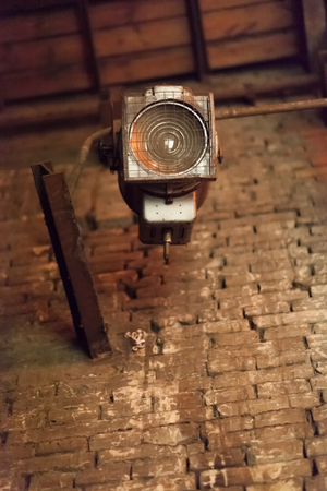 searchlight: Extinct old searchlight, behind the scenes of a theatrical scene, on a background of a brick wall.