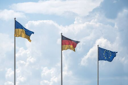 flutter: Flags of Ukraine, Germany and the European Union flutter on wind, in sunny day, against the background of cumulus clouds. Stock Photo