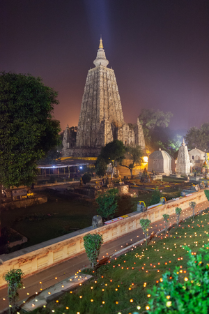 gautama: The place of an enlightenment of Buddha, Mahabodhi Temple in beams of night illumination and in festive decoration in honor of a menlam and celebration of Buddhist new year. Stock Photo