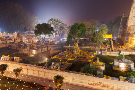 The place of an enlightenment of Buddha, Mahabodhi Temple in beams of night illumination and in festive decoration in honor of a menlam and celebration of Buddhist new year. Stock Photo