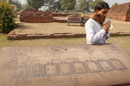 sutra: Archaeological heritage of India, ruins of university of Nalanda on February 2, 2014. At a stone with the scheme of excavation, the Indian guide has earned reward.