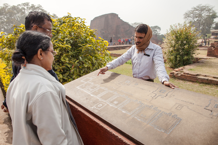 tantra: Archaeological heritage of India, ruins of university of Nalanda on February 2, 2014. At a stone with the scheme of excavation, the Indian guide shows to tourists an sites of objects.