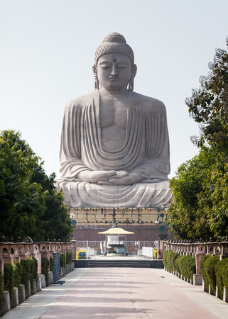 tantra: The tiny chipmunk has run out on a path in front of The Giant Buddha Statue in Bodhgaya, Bihar, India. The statue is 25 m or 82 ft high in meditation pose or dhyana mudra seated on a lotus in open air. Located near Mahabodhi Temple.