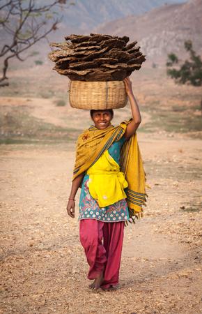 biomasa: La niña rural lleva en la cabeza una cesta con el combustible natural hecho de excremento de vaca y paja. Es el tipo de combustible más económico y extendido para la calefacción y la cocina, en los estados del norte de la República de la India. El 30 de enero de 2014, Bihar.