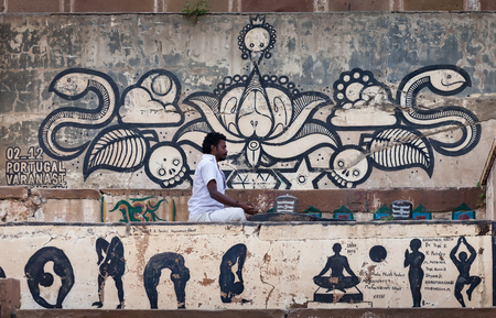 sadhu: The person practicing yoga in white clothes, sits in a meditation pose near a shiva-lingam, in front of the wall covered with drawings of graffiti. Below, under him, are represented some asanas from yoga complexes. February 6, 2014. Varanasi. India.