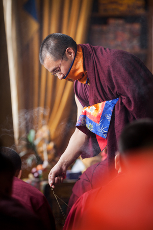 The Buddhist monk wearing spectacles fumigates with ritual incense the room during the ceremony of dedication which is carried out by the His Holyness the 17th Gyalva Karmapa Triley Thaye Dordje at institute of KIBI in Delhi. India. January 25, 2014.
