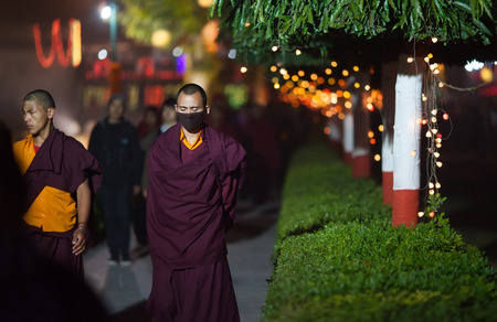 gaya: January 31, 2014. Bodh Gaya. India. Monks-pilgrims in traditional clothes, make evening kora (a ritual round of the temple or a shrine) during an annual menlam at Mahabodhi Temple. Editorial
