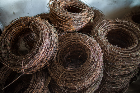unfreedom: The rusty rings of an old barbed wire lying in military warehouses waiting for hour of triumph for use to destination - to stop the enemy. Stock Photo