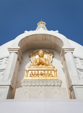 Gilded bas-relief of Buddha in a pose of a dharmachakra mudra. It is located on a facade of Shanti Stupa (Peace Pagoda), on a slope of the mountain of vulture where Buddha Shakyamuni gave lectures about a Dharma. City of Rajgir, State of Bihar, India.