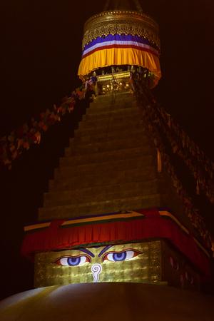 Buddhas eyes depicted on a buddhist stupa Boudnath in night illumination. In a Kathmandu, capital of the Nepal. Stock Photo