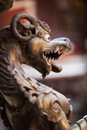 The growling mythical lion made of bronze, in the ancient Buddhist temple Golden Templ, Lalitpur, Katmandu, Nepal. Stock Photo