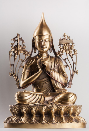 tantra: Bodhisattva Avalokiteshvara - a figure from bronze sitting on a white background in a pose of a lotus, a hands in  Dkharmachakra-mudra.