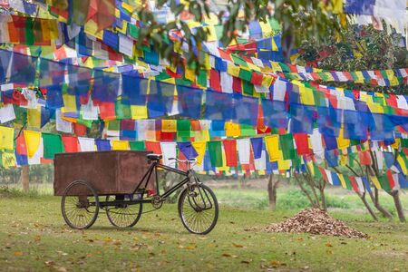 The rickshaw on the way to an enlightenment. Old tricycle - the rickshaw used for cargo hauling, stands in the shadow of Buddhist prayful flags - Lungta, hanging on the territory of the temple complex of mother of Buddha - Maya Devi, in Lumbini, Nepal.