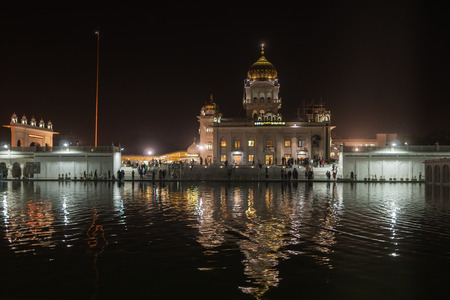 Night view of one of the main Sikh shrines of Delhi - Gurudwara Bangla Sahib. The main building of the temple is illuminated and is reflected in Sarowar pond water. Stock Photo