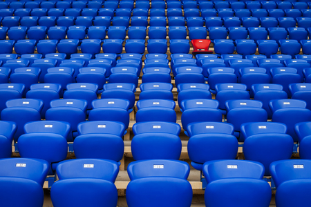 One red armchair among blue armchairs in the stands of stadium as an identity symbol, as an appeal to be not such as everything, to mark out from the uniform crowd. Editorial