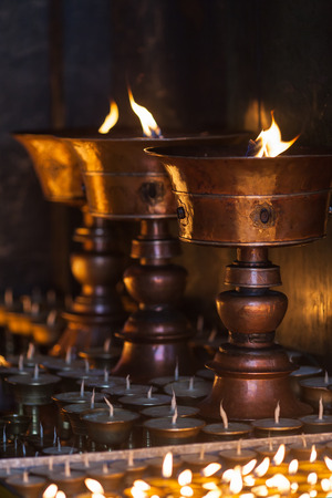 Grote en kleine boterlampen branden in de boeddhistische tempel, als vuurgeschenk van pelgrims.