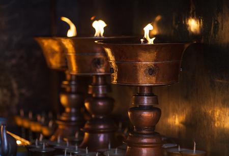Grote olielampen branden in de boeddhistische tempel, als vuurgeschenk van pelgrims. Stockfoto