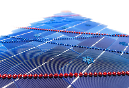 Blue elements of solar panels are laid out in the form of a traditional Christmas tree and festively decorated with snowflakes and blue and red threads of beads.
