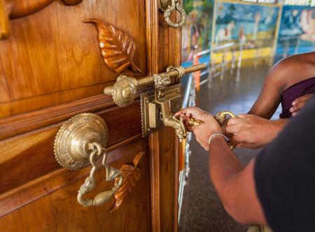 Dois pares de mãos masculinas abrem a grande fechadura nas portas do templo budista no Sri Lanka Foto de archivo - 91875381