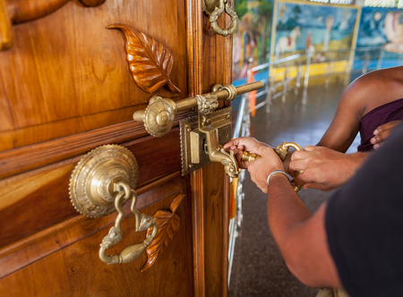 Two pairs of male hands open the big lock on doors of the Buddhist temple in Sri Lanka Stock Photo