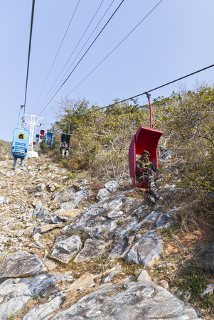 The Indian police officers carry out the protection of the public order, moving by means of the ropeway, Radzhgir, the State of Bihar, India, on February 1, 2014.