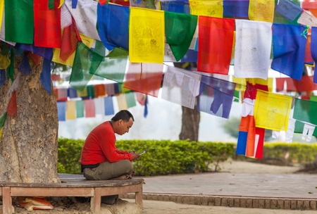 The person with enthusiasm looking in the smartphone, sitting in a lotus pose under a tree with a set of Buddhist prayful flags. Lumbini, Nepal, on March 2, 2017 Editorial