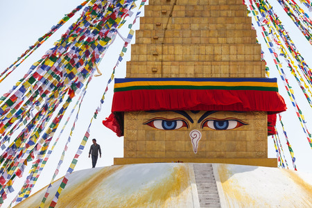 The worker strolls by the top of the stupa of Bouda, near closely watching Buddhas eyes. Boudnath, Kathmandu, Nepal, on March 5, 2017.