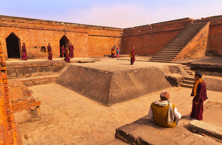 Group of Buddhist pilgrims - the Tibetan monks, in the yard of the ancient Buddhist university Nalanda, India, Rajgir, on February 2, 2014.