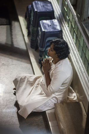 The woman prays in the Buddhist temple Gangaramaya, sitting on a floor in a semi-lotus pose. Colombo, Sri Lanka, on January 20, 2017 Editorial