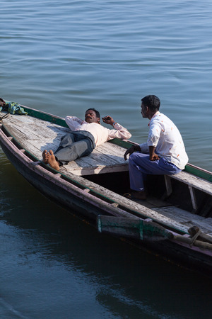 Midday rest of the Indian boatmen onboard the wooden boat, before flows of tourists, on the bank of Ganges. India, Varanasi on February 6, 2014